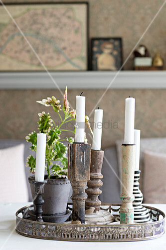 Various old candlesticks on delicate metal tray