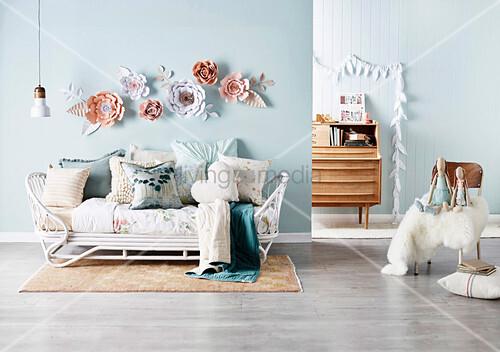 Rattan-Tagesbett mit Kissensammlung vor hellblauer Wand mit dekorativen Papierblüten