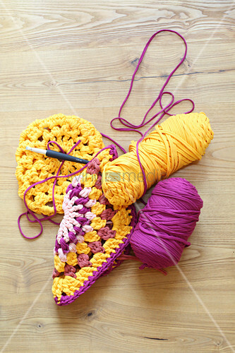 Granny squares crocheted from pink and yellow jersey yarn and reels of yarn