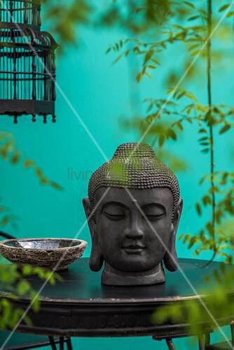 Buddhakopf auf schwarzem Tisch und Blätterranken vor türkiser Wand