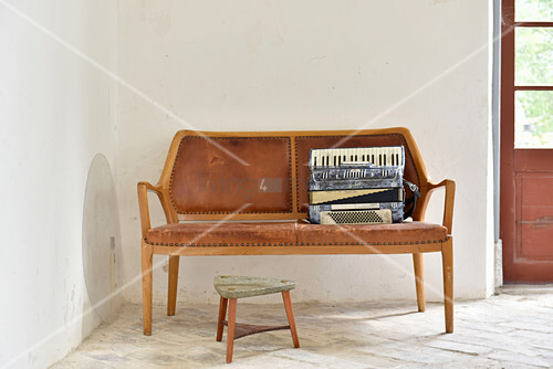 Accordion on wooden bench with leather upholstery