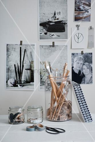 Gläser mit Büroutensilien vor einer Wand mit Schwarz-Weiß-Fotos
