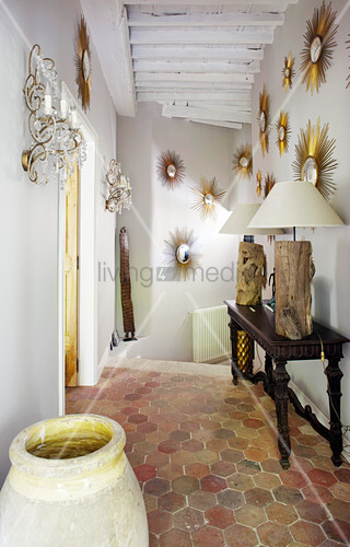 Collection of sunburst mirrors in hallway with honeycomb floor tiles