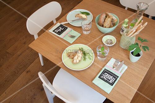 Bestecktaschen mit Namensschildern auf dem mintgrün gedeckten Tisch