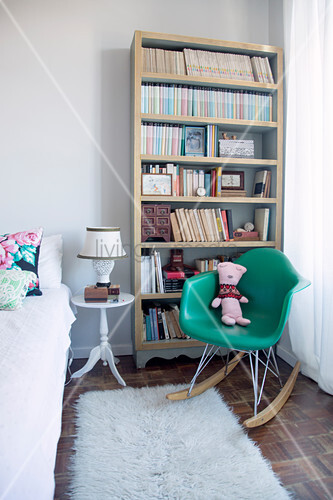 Green designer rocking chair in front of bookcase in bedroom