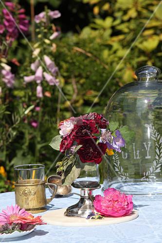 Blumensträußchen im Glaspokal auf dem Gartentisch