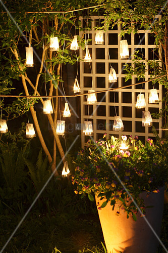 Arrangement of lanterns made from wire and tealights in garden