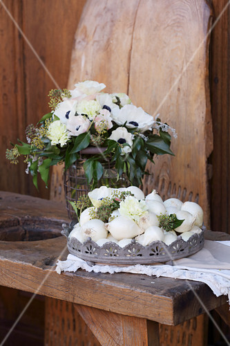 Bouquet of anemones, carnation and ivy next to basket of onions