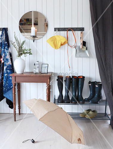 Board wall, old table and shoe rack in rustic hallway