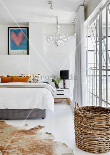 Doppelbett in weißem Schlafzimmer, im Vordergrund Tierfellteppich und Korb