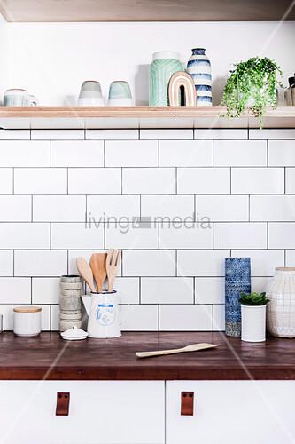 Küchenutensilien auf Holzarbeitsplatte, darüber weiße Wandfliesen und Regal
