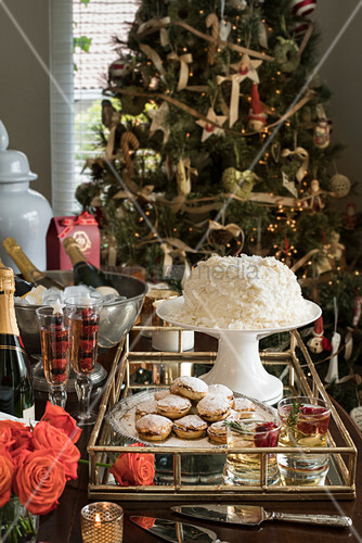 Mince pies and drinks on tray in front of Christmas tree
