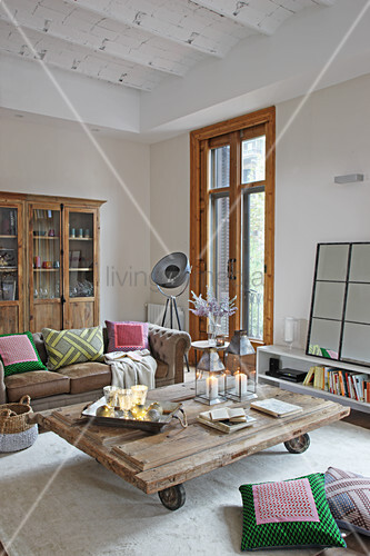 Rustic coffee table on castors in living room with vaulted ceiling
