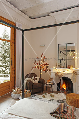 Cosy armchair and open fireplace with four-poster bed in foreground