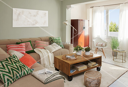 Colourful cushions on sofa in living room in muted shades