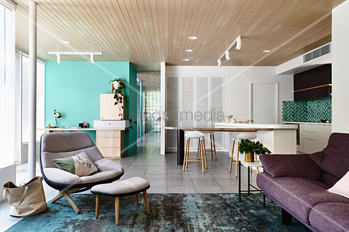 Lila Sofa und Designersessel mit Fußhocker in offenem Wohnraum