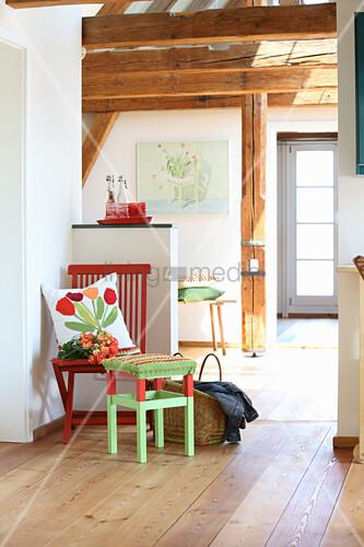 Roter Stuhl mit selbst genähtem Dekokissen und Hocker mit gehäkeltem Bezug