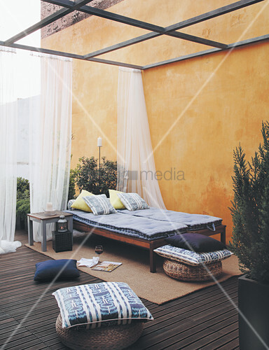 Loungers with mattresses and cushions on terrace next to yellow exterior wall