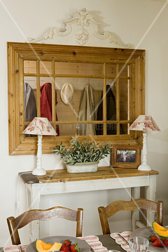 Two table lamps on console table below interior window leading to cloakroom