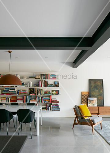 Moderner Wohnraum mit Esstisch vor der Bücherwand – Bild kaufen ...