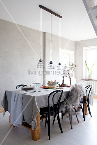 Set table in dining room in wintry shades with grey wall