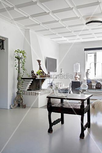 Wohnzimmer in Weiß mit Kassettendecke und offenem Kamin