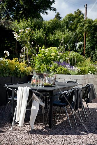 Tisch und Stühle im Hof vor blühenden Hochbeeten