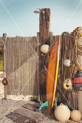 Surfboard leaning against fence next to outdoor shower and buoys