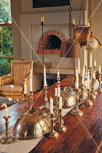 Silver candlesticks and silver plate covers on wooden table