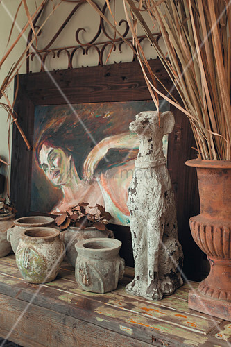 Dog figurine and old stone pots in front of painting of woman