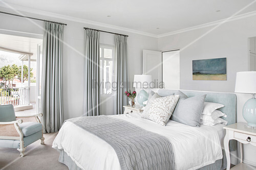 Elegant bedroom in pale blue-grey with partition wall at head of bed