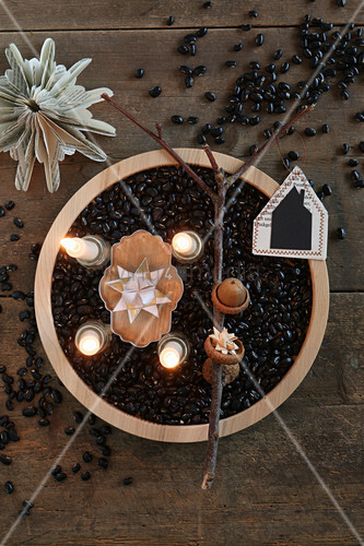 Advent arrangement of four lit candles amongst black beans in wooden dish