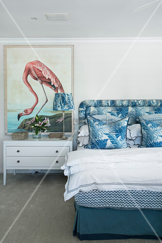 Picture of flamingo in bedroom with blue and white jungle-patterned textiles