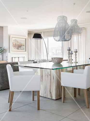 White upholstered chairs around modern glass and wood dining table