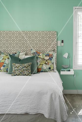 Verschieden gemusterte Kissen auf dem Bett vor mintgrüner Wand