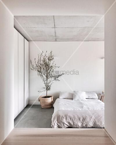 Blick durch tunnelartigen Durchgang ins weiße Schlafzimmer