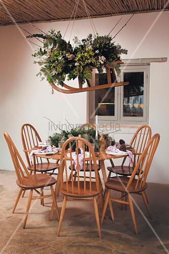 Flower arrangement on sledge above festively set table