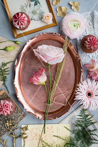 Pink flowers, copper tray, vintage cards and cupcakes on grey surface