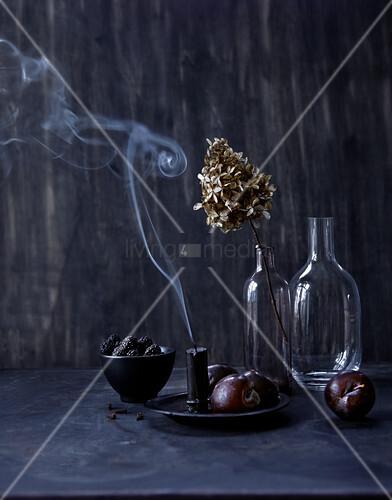 Still-life arrangement of dark fruit, glass bottles and candle smoke