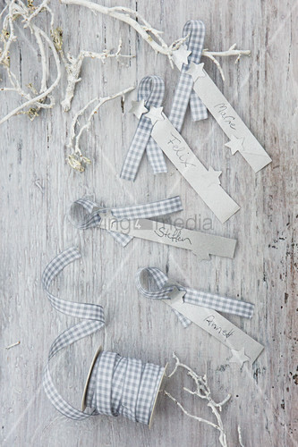 Festive name tags handmade from strips of paper and gingham ribbon
