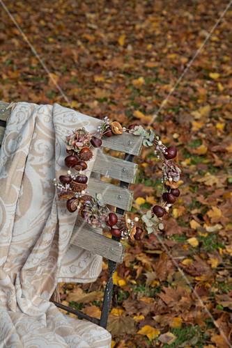 Gartenstuhl mit DIY-Kranz aus Kastanien und Decke
