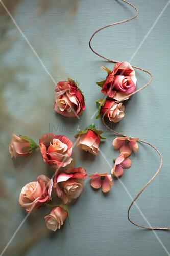 Rosenblüten und Bindfaden auf grauem Untergrund
