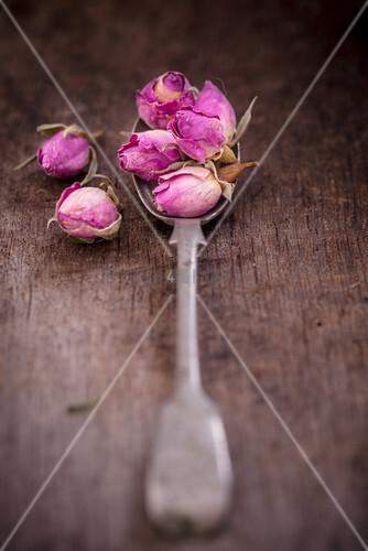 Dried rose buds on vintage spoon