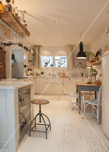 Large white country-house kitchen with dining area