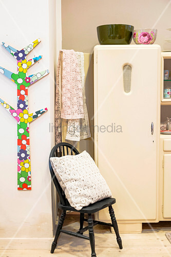 Stylised plywood tree covered with colourful foil, cushion on chair and cream fridge