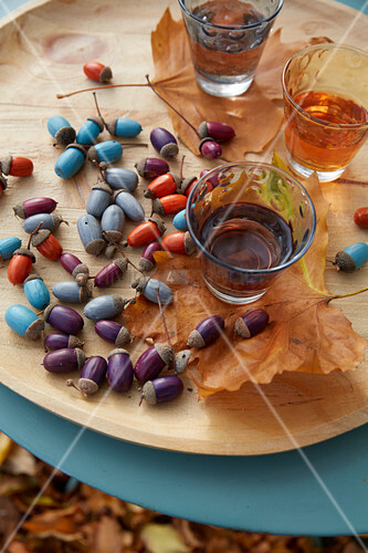 An autumnal table decoration made from painted acorns