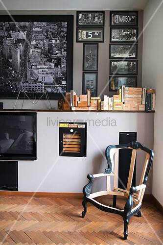 Antique chair frame in corner below collection of black and white photos on wall