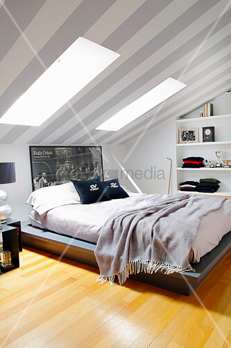 Double bed in attic room with grey and white stripes wallpaper on ceiling