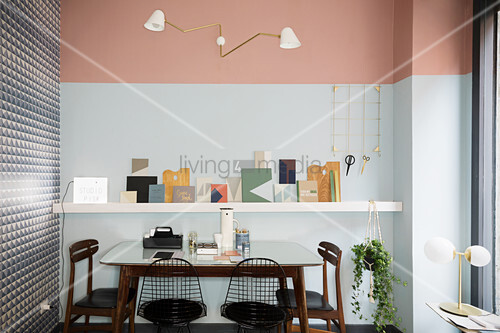 Table and various chairs in front of floating shelf on two-tone wall