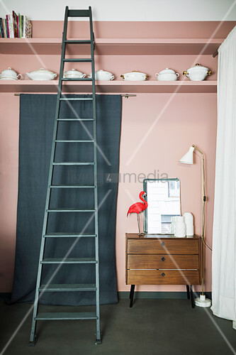 Standard lamp, chest of drawers and length of green fabric below china on shelf and ladder against pink wall